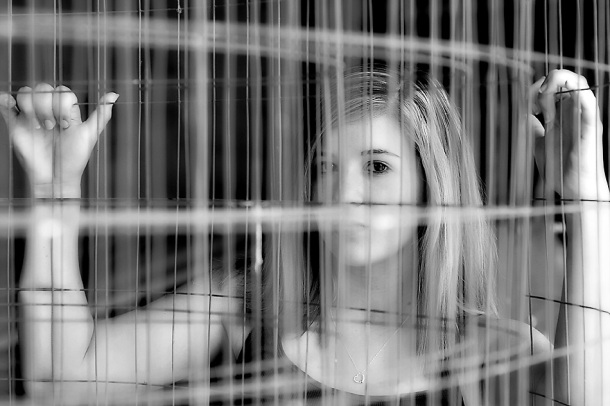 black and white image of girl thru fencing