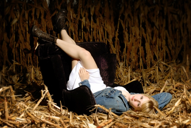 portrait of a senior girl laying in a cornfield