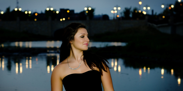 Senior girl with streetlights reflected on water