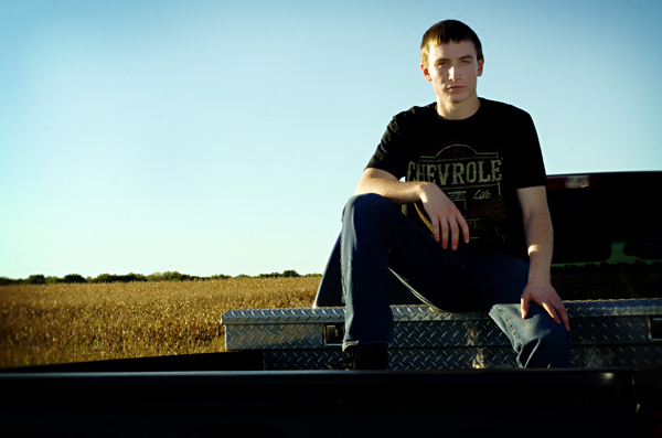 2016 senior guy, with a field and his truck