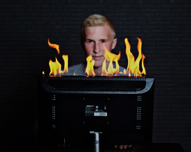 senior with flaming computer monitor